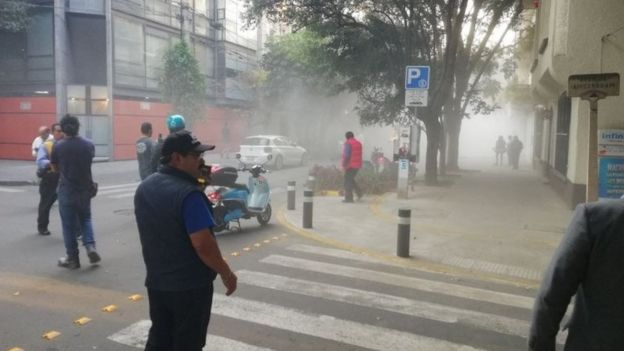Clouds of dust are seen in the air as residents gather on the streets of Mexico City