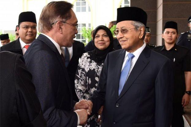 Малазийский политик Анвар Ибрагим пожимает руку с премьер-министром Малайзии Махатхиром Мохамадом в Национальном дворце в Куала-Лумпуре, Малайзия, 16 мая 2018 года.