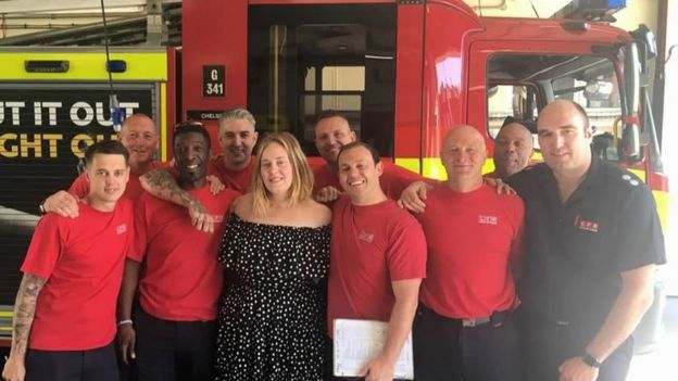 Picture of Adele with fire fighters standing in front of a fire engine