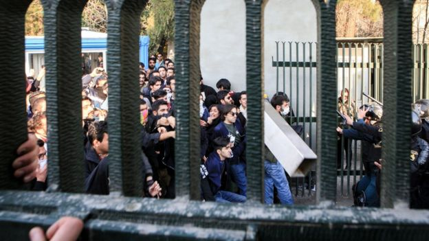 Iranian students clash with riot police during an anti-government protest around the University of Tehran. One man hold a concrete block in front of police carrying batons and shields.