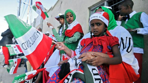 People wave flags as soldiers and other military personnel of Somalia's breakaway territory of Somaliland march past during an Independence day celebration parade in the capital, Hargeisa on May 18, 2016