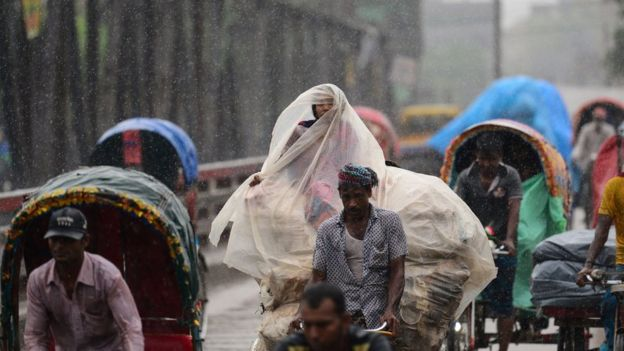 Bangladeshi rickshaw pullers make their way with commuters during a monsoon rain in Dhaka on 11 June 2017