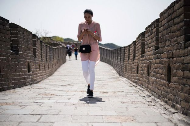 A Chinese lady walks as she types on her smartphone on the Great Wall in Mutianyu, near in Beijing on 23 April 2016.