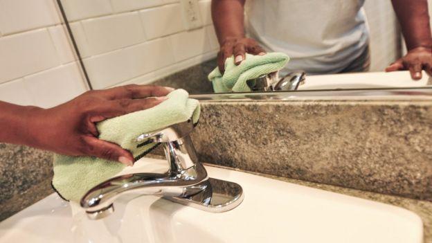 Mulher limpando pia