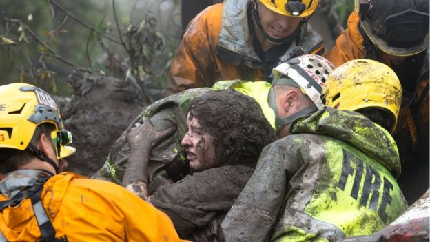 Mud-covered woman being lifted by four emergency responders