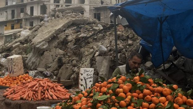 A man pictured at a market stall in Aleppo surrounded by rubble