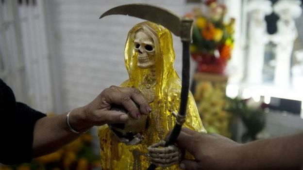 Devotees touch the figures of Santa Muerte (Saint of Death) before the central altar asking for favours during the main celebration in the market of one of the most dangerous neighbourhoods, known as Tepito in Mexico City, on 1 November, 2012.