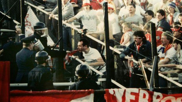 Policía e torcedores em um estádio