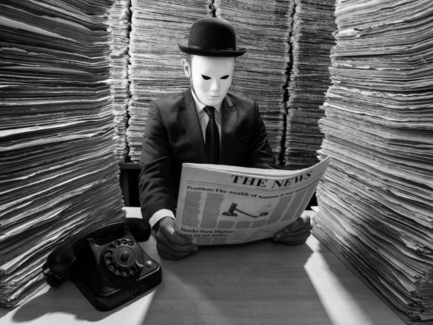 A man wearing a mask reads a newspaper