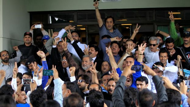 Opponents of Pakistan's Nawaz Sharif shout slogans as they exit the Supreme Court in Islamabad