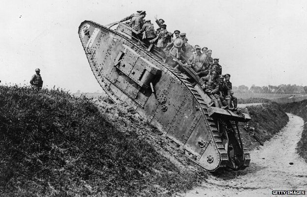 British troops riding on the back of the Mark IV tank as it crawls over a trench ledge in 1918