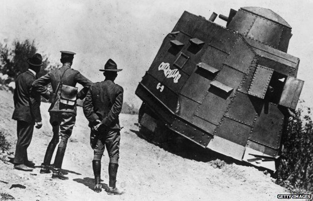 Three men look on as a US tank appears to be stuck on the side of a road
