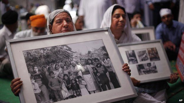 Indian Sikh women hold photographs of riot victims as they protest the acquittal of ruling Congress party leader Sajjan Kumar, in New Delhi, India, 7 May 2013