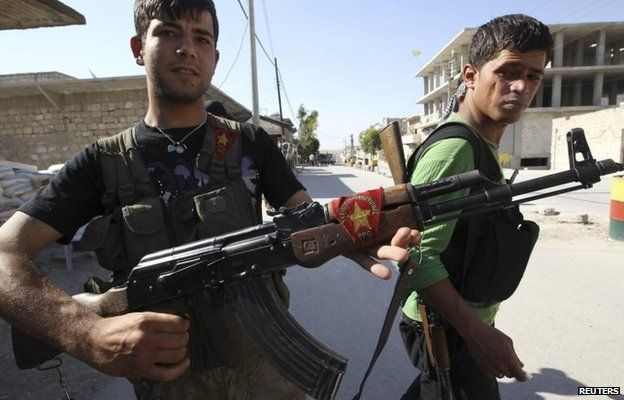 A Kurdish fighter from the Popular Protection Units (YPG) shows his weapon decorated with its flag in Aleppo, Syria (7 June 2014)