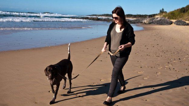 A Filtered Media employee walking her dog on a beach