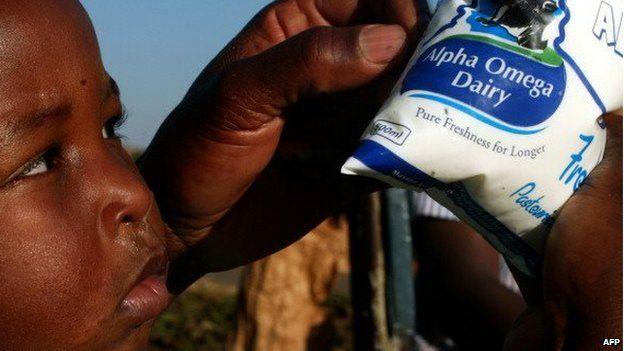 Un niño junto a uno de los productos de la empresa de lácteos de Grace Mugabe en un mercado de Harare.