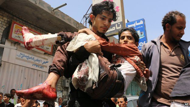 A man carries a boy who was injured during a crossfire between tribal fighters and Shiite
