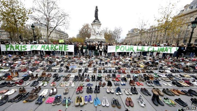 "Banners which read ""Paris marches for climate change"" are displayed in front of pairs of shoes placed at the Place de la Republique in Paris"