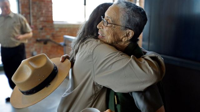 National Park Service Ranger Betty Reid Soskin is embraced by a volunteer Tuesday, July 12, 2016, at the Rosie the Riveter World War II Home Front National Historical Park in Richmond, Calif.