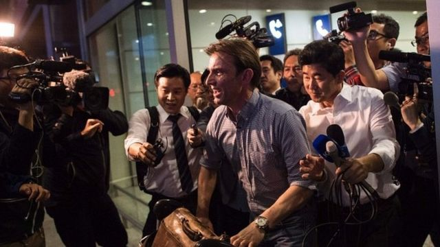 Rupert Wingfield-Hayes surrounded by media at Beijing airport