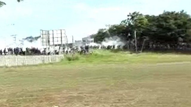 Police officers amid smoke in distance at Papua New Guinea university - 8 June 2016