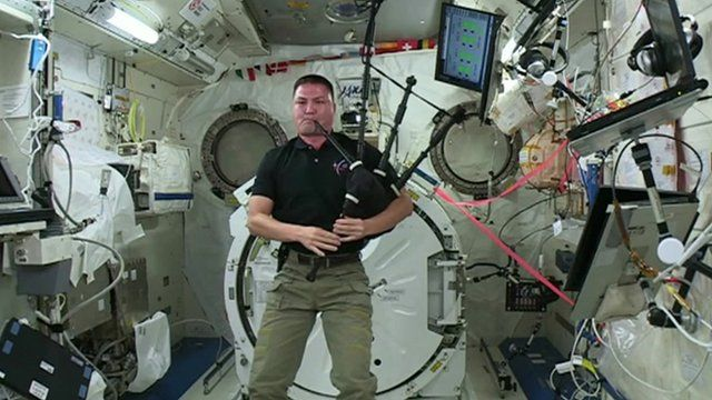 America astronaut playing bagpipes in space.