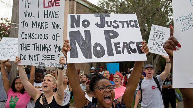 Police and protesters demonstrate in a residential neighbourhood in Baton Rouge, La. on Sunday, July 10, 2016.