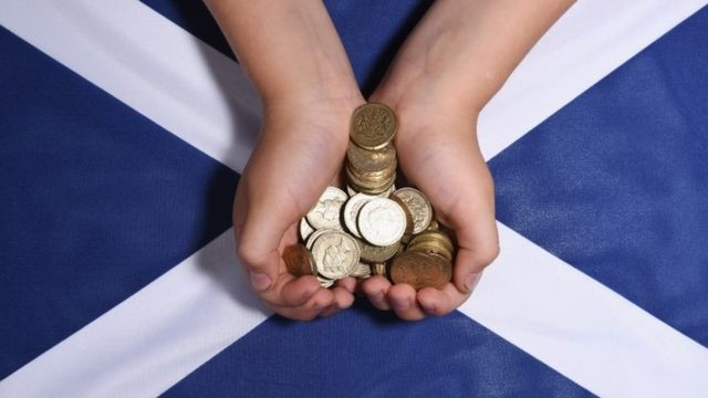 Pound coins are placed on the Scottish national flag