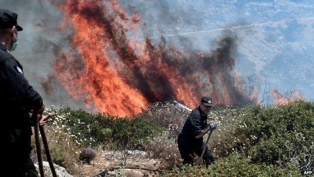 Firefighters battle a fire in Athens on 17 July 2015
