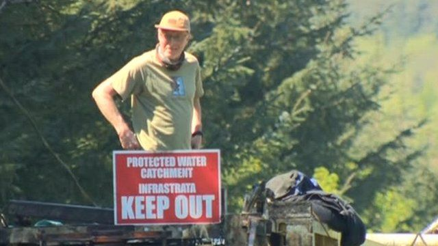 Mark Chapman, a protester involved in a stand-off between environmentalists and a company, Infrastrata, which wants to drill an exploratory oil well at a County Antrim forest, has climbed on one of the drills.