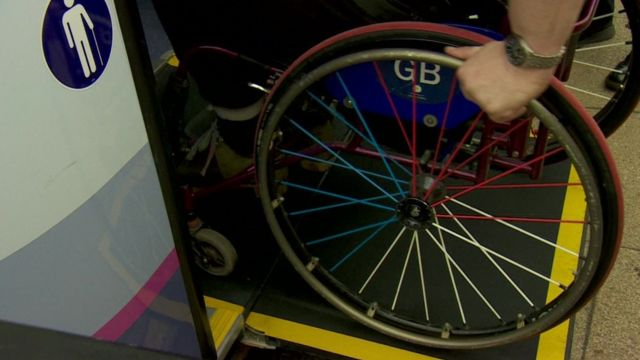 Wheelchair user boarding bus on special ramp