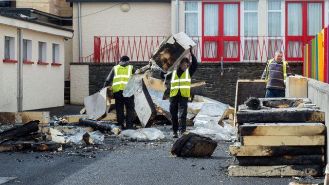 Workers clear the burnt debris from the schoolyard