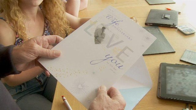 Chris Roberts holding his anniversary card for his wife