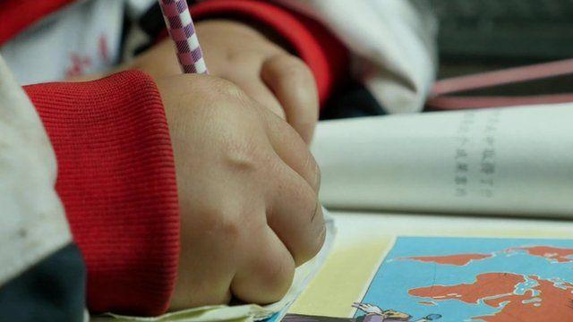 A child's hand writes