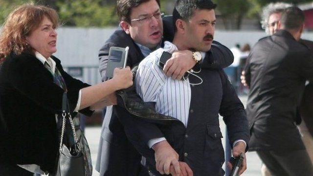 Dilek Dundar (L), the wife of editor-in-chief of Turkish newspaper Cumhuriyet daily Can Dundar, trying to stop a gunman as Can Dundar (R) is protected by another man on May 6, 2016 in Istanbul