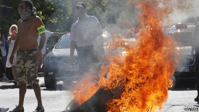 Striking taxi drivers in Paris standing by a burning tyre during a protests against app-based taxi company Uber