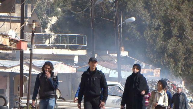 Residents in al-Waer district in Homs walk in a war-ravaged street