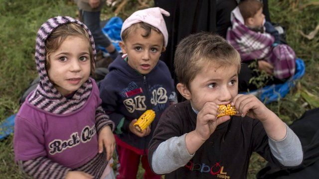 Three Syrian children in Hungary, one of them eating raw corn