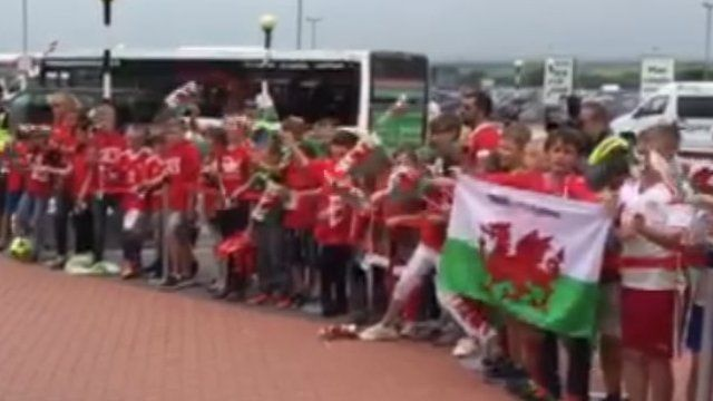 Pupils from Cardiff's Ysgol Treganna give a rousing send-off to the Wales team as they depart from Cardiff Airport.