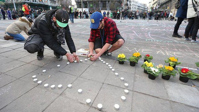 People put out candles and flowers in Brussels to pay tribute to the victims of the attacks.