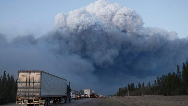 A cloud of smoke rises from the wildfire