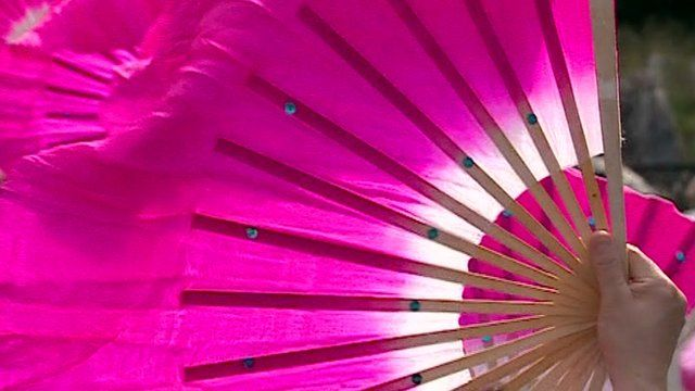 A large pink fan waved by a dancer.