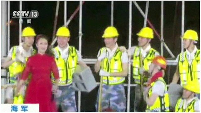 Female singer surrounded by male singers dressed as construction workers, as one of them proposes, on stage in the Spratly Islands (May 2016)