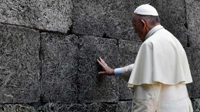 Pope Francis prays at the Death Wall