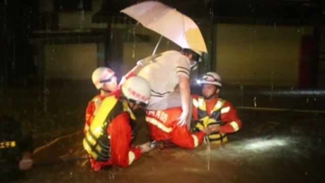 A woman is rescued from her flooded home