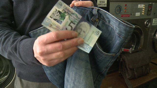 £5 note being put in jeans pocket