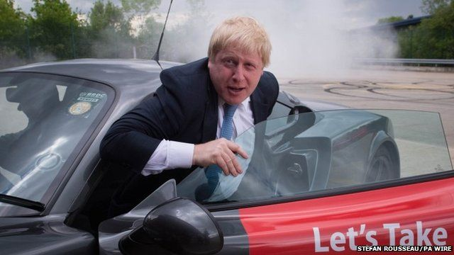 """Boris Johnson emerges from a Ginetta sport car after the company's Chief Executive Lawrence Tomlinson performed a series of """"doughnuts"""" as the former Mayor of London visited the factory in West Yorkshire"""