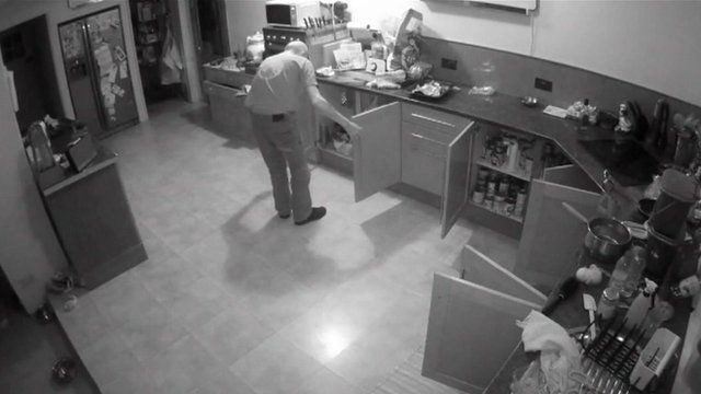 CCTV of Chris Roberts opening cupboards in his kitchen