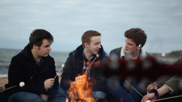 Young people sitting at a campfire