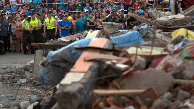 Residents look at rescue workers toil in an earthquake collapsed building in Manta, Ecuador
